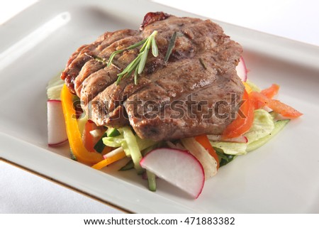 meat with radish and vegetables on plate