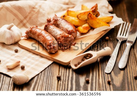 meat with vegetables , fried homemade sausage with roasted potatoes with garlic and pepper on a wooden background - stock photo