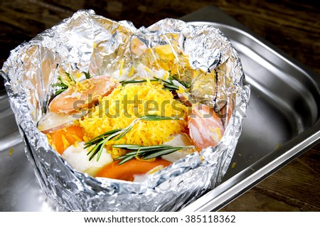 Meat with vegetables in foil on Protvino. Wooden background.