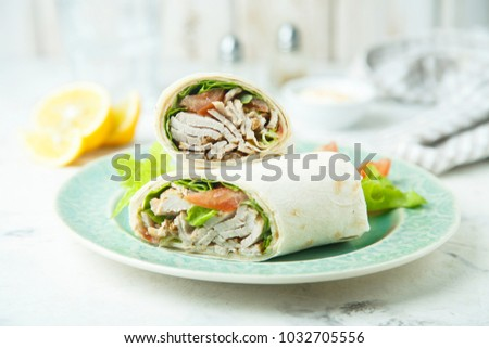 Meat wraps with green salad and tomato