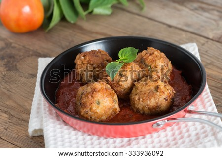 Meatball with tomato sauce in pan.