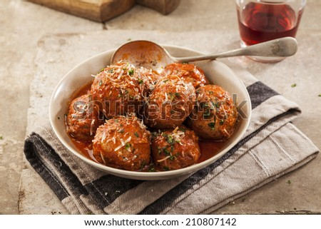 Meatballs cooked in tomato sauce in bowl on grey backround