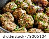 Meatballs cooking in a pan, with parsley scattered on top.  Delicious! - stock photo