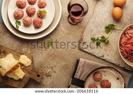 Meatballs cooking with mince, parsley, parmesan, wine and eggs. - stock photo