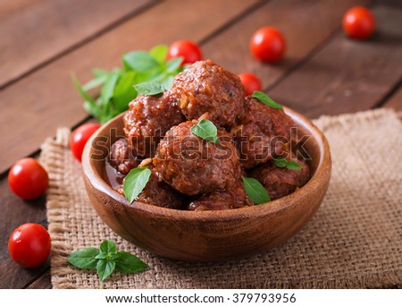 Meatballs in sweet and sour tomato sauce and basil in a wooden bowl