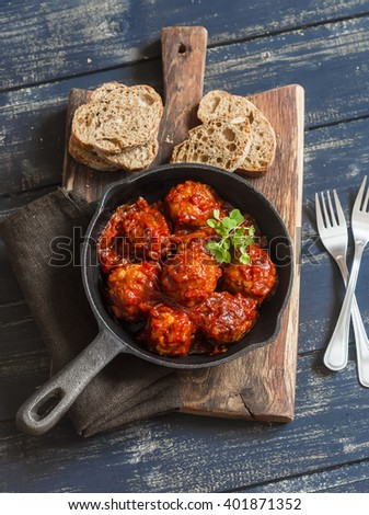 Meatballs in tomato sauce in a pan on rustic wooden dark background - stock photo
