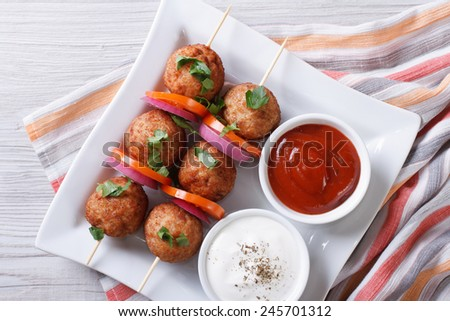 meatballs on skewers with vegetables and sauce on a plate close-up. horizontal view from above  - stock photo