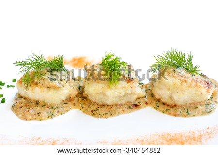 Meatballs served in a dill sauce on a white plate.