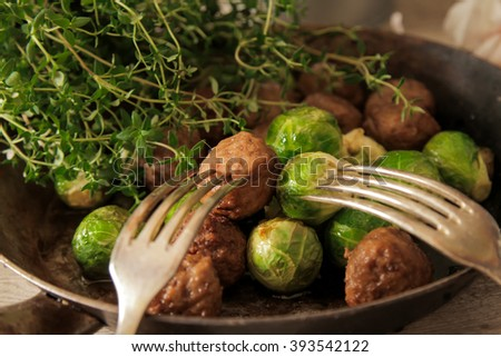 meatballs with cabbage and basil in a frying pan on 