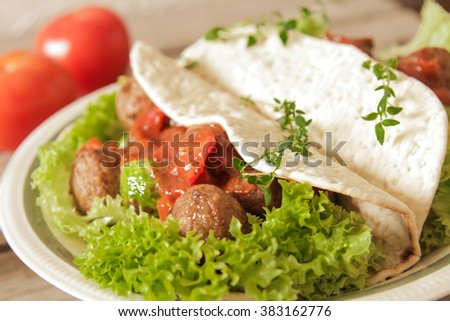 meatballs with cabbage on lettuce in pita bread  a wooden background