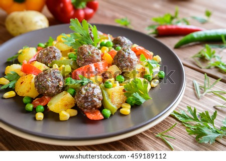 Meatballs with fried potatoes, pepper, corn and pea