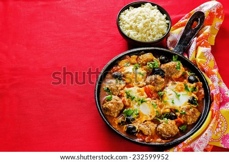 meatballs with olives and egg in tomato sauce. Moroccan dish. tinting. selective focus - stock photo