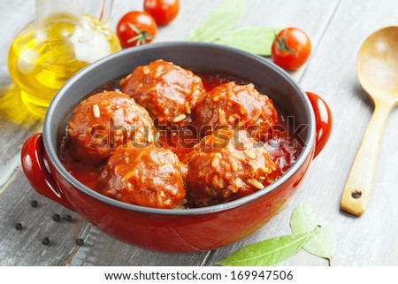 Meatballs with rice and tomato sauce in the pot - stock photo