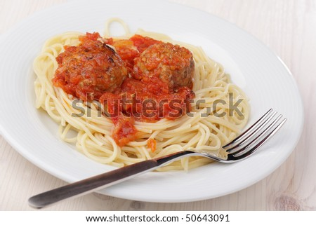 Meatballs with tomato sauce and spaghetti on white plate