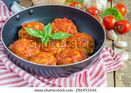 Meatballs with tomato sauce in frying pan - stock photo