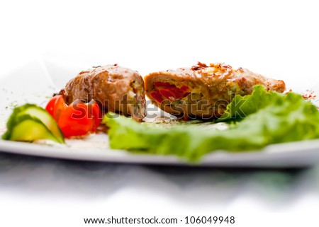Meatloaf with vegetables on a white plate decorated with a leaf of lettuce on a white background isolated. A series of food in a restaurant close-up