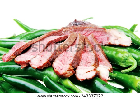meaty food : roasted red meat steak sliced on a green hot chili peppers on a white back - stock photo