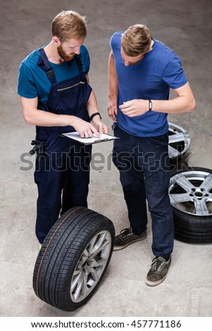 Mechanic and client making order in auto service.