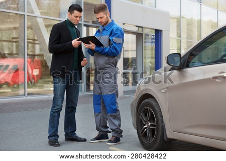 Mechanic and Customer Discussing Problem With Car. Auto Repair Shop - stock photo