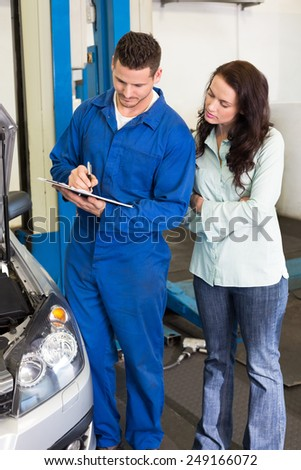 Mechanic and customer standing together at the repair garage - stock photo