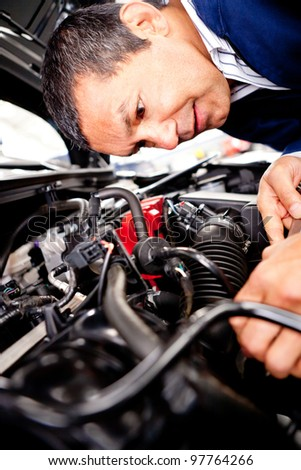 Mechanic at the garage fixing a car engine - stock photo