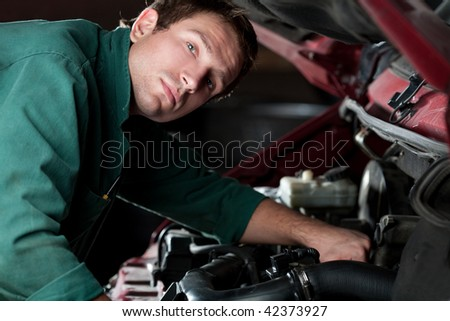 Mechanic at work fixing car in auto service