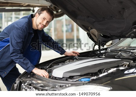 Mechanic at work. Young cheerful mechanic working at the repair shop and smiling at camera - stock photo