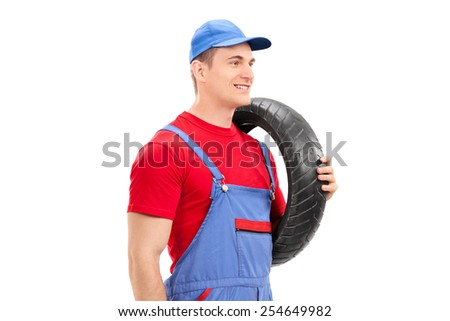Mechanic carrying a tire and walking isolated on white background - stock photo