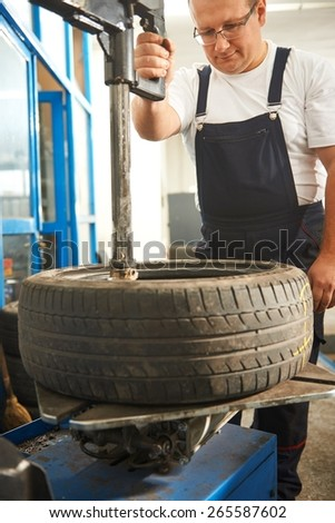 Mechanic changing car tire - stock photo