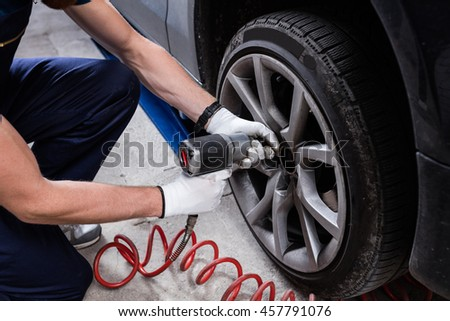 Mechanic changing car wheel with impact wrench at service.