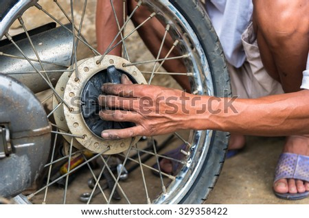 mechanic changing motorcycle tire by traditional method - stock photo