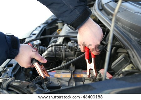 mechanic changing the battery of a car - stock photo