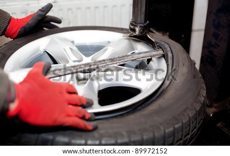 Mechanic changing tire in car service. Tire rotation machine