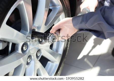 Mechanic changing wheel on car with a wrench. - stock photo