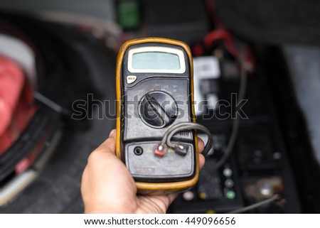 Mechanic checking a car battery level with  voltmeter in garage - stock photo