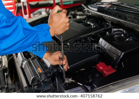 Mechanic checking and fixing a broken car in car service garage with copy space - stock photo