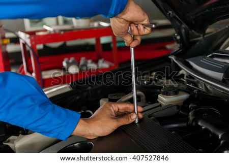 Mechanic checking and fixing a broken car in car service garage with copy space (focus on screwdriver) - stock photo