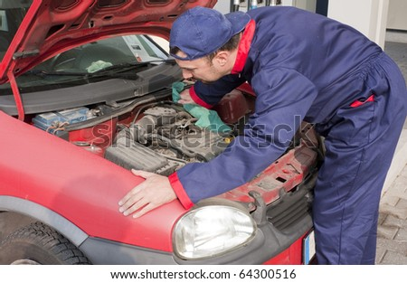 Mechanic Checking Oil Level at Gas Station - stock photo