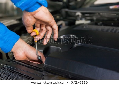 Mechanic checking oil level in a car service garage - stock photo