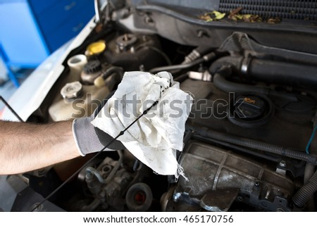 Mechanic checking the oil in a car in a workshop