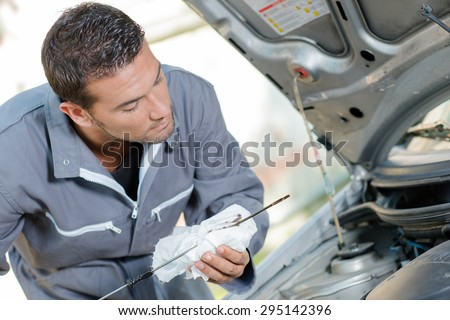 Mechanic checking the oil level of a car - stock photo