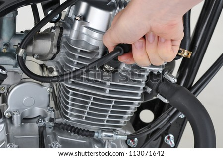 mechanic checking the spark plug lead on a motorcycle - stock photo