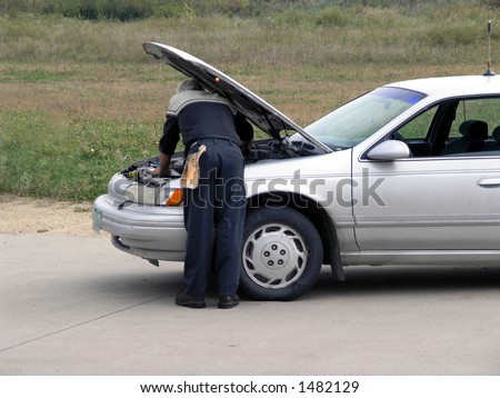 Mechanic checks out car under hood. - stock photo