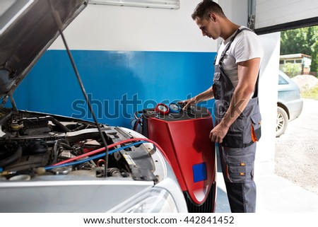 Mechanic checks the air conditioner at service station