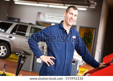 Mechanic: Cheerful Worker By Shop Computer - stock photo