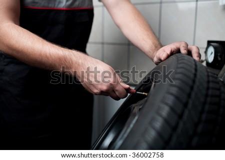 Mechanic deflating vehicle tyre closeup - stock photo