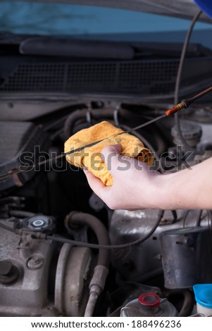 Mechanic during checking oil level in garage - stock photo