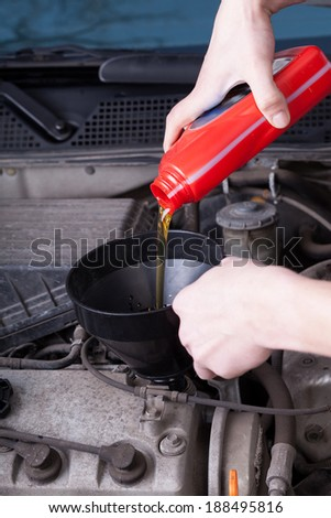 Mechanic during pouring motor oil in garage