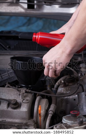 Mechanic during pouring oil into car engine - stock photo