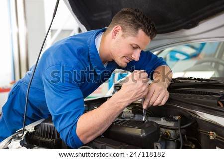 Mechanic examining under hood of car at the repair garage